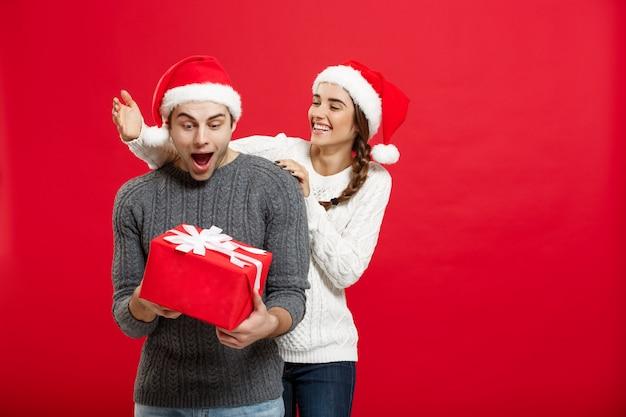 Augen der jungen frau, die mann mit der hand bedecken und großes geschenk der überraschung geben