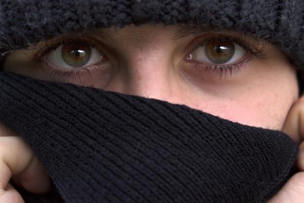 Augen des jungen mannes mit mütze und schwarzem schal