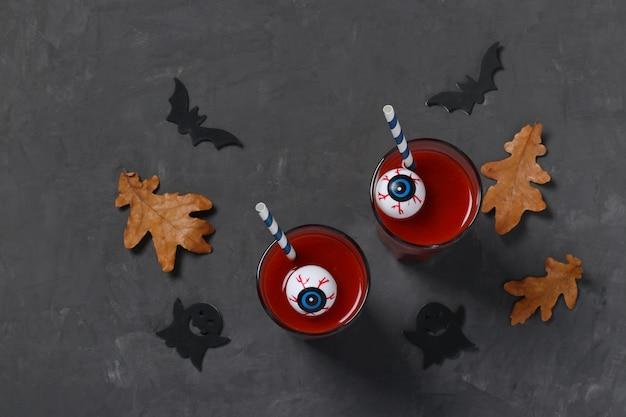 Augen im glas mit tomatencocktail auf dunklem tisch für herbstferien halloween. draufsicht.