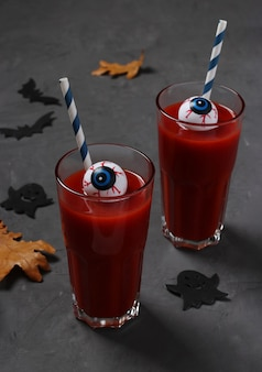 Augen im glas mit tomatencocktail auf dunklem tisch für herbstferien halloween. nahansicht. vertikales format.