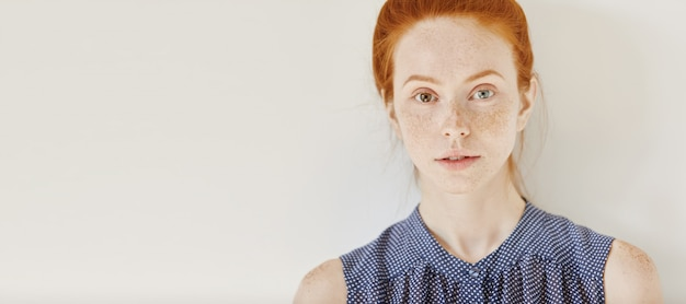 Augen in verschiedenen farben: blau und braun. zarte sommersprossige junge kaukasische frau mit heterochromia iridum, die ärmelloses hemd mit flecken trägt, die ruhe in innenräumen haben und mit einem schwachen lächeln schauen