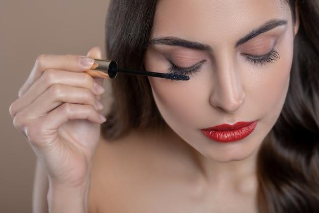 Augen makeup. junge hübsche dunkelhaarige frau beim auftragen von wimperntusche auf augenlider, die mit daunenlidern aufmerksam sind