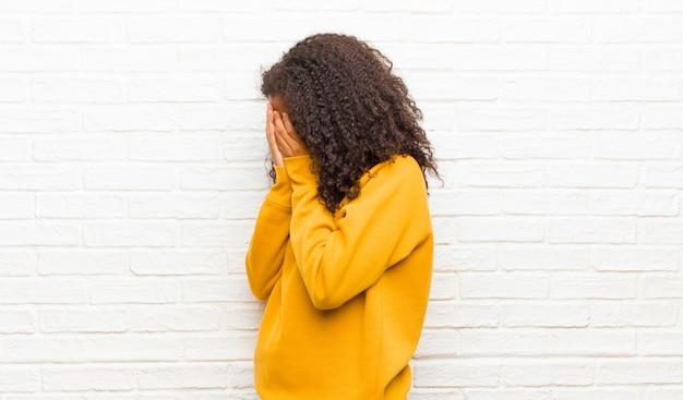 Augen mit händen bedecken mit einem traurigen, frustrierten ausdruck von verzweiflung, weinen und seitenansicht