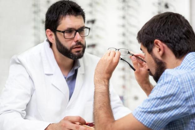 Augenarzt bietet brille zum ausprobieren an