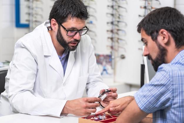 Augenarzt, der einem kunden ein tablett mit verschiedenen gläsern zeigt.
