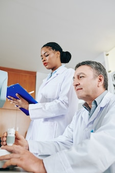 Augenarzt, der refraktometer-sehtestgerät verwendet, wenn krankenschwester medizinische karte des patienten ausfüllt