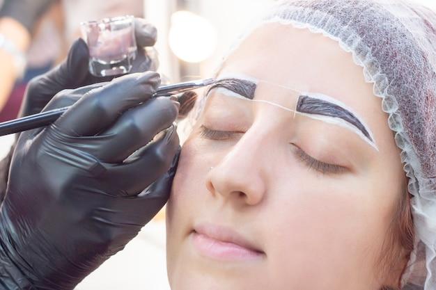 Augenbrauen färben. schönheitssalon. das mädchen liegt mit geschlossenen augen beim färben der augenbrauen. der augenbrauenmeister trägt einen pinsel auf die augenbrauen des kunden auf.