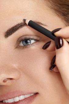 Augenbrauen formen. junge frau der schönheit mit brauenstift. nahaufnahme des schönen mädchens mit professionellem make-up, das brauen mit augenbrauenstift konturiert.