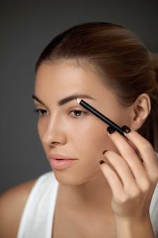 Augenbrauen make-up. schöne frau mit perfektem make-up, das die brauen mit augenbrauenstift konturiert. nahaufnahme des weiblichen vorbildlichen schönheitsgesichtes mit glatter haut auf grauem hintergrund.