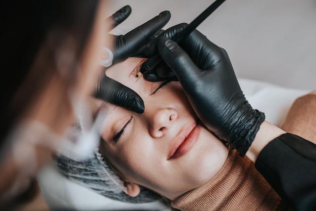 Augenbrauen-microblading-konzept, augenbrauen-permanent-make-up-verfahren. schönheitsexperte trägt aufgrund der coronavirus-pandemie eine abgeschirmte und schützende gesichtsmaske.