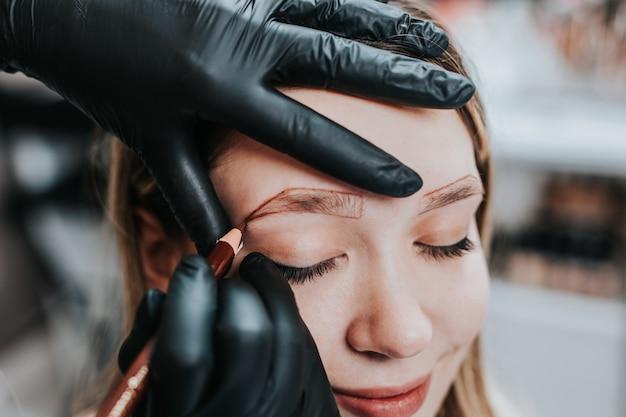 Augenbrauen microblading-konzept. kosmetikerin, die junge frau für augenbrauen-permanent-make-up-verfahren vorbereitet.