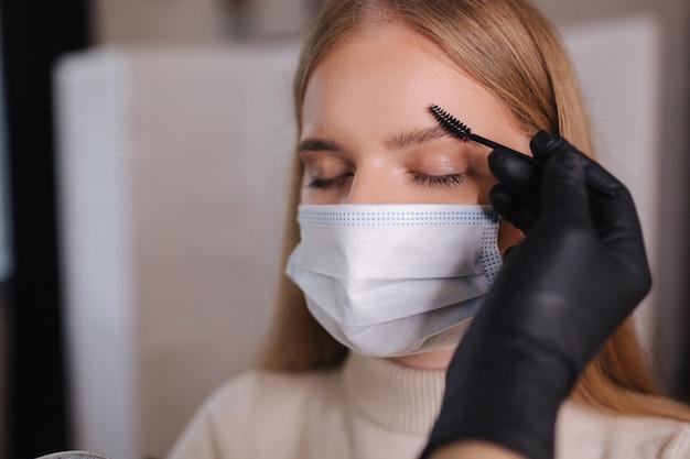 Augenbrauen- und make-up-meister in schutzmaske geben form zum herausziehen mit einer pinzette