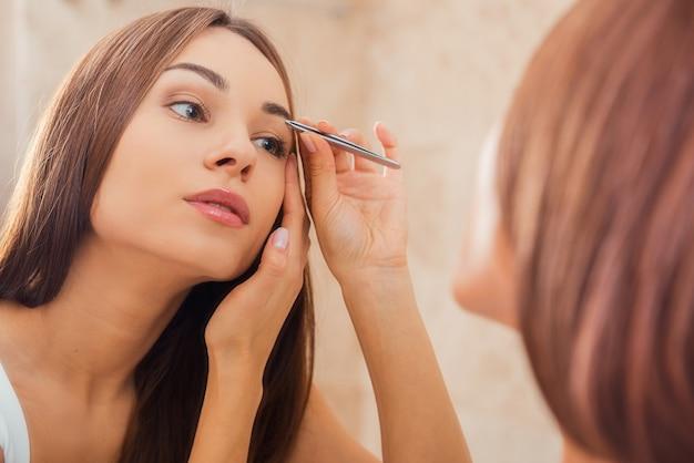 Augenbrauen zupfen. schöne junge frau, die ihre augenbrauen zupft, während sie den spiegel betrachtet