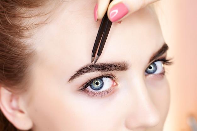 Augenbrauen zupfen und malen in einem schönheitssalon.