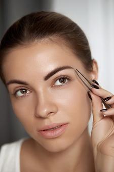 Augenbrauenkorrektur. augenbrauen zupfen. schöne junge frau mit pinzette. modell mit schönheitsgesicht.