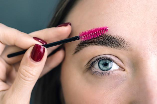 Augenbrauenkorrektur in einem schönheitssalon. kombinieren sie ihre augenbrauen. die augenbrauen der frau. schönheit und pflege. schönes mädchen mit augenbrauenbürste. mädchen mit natürlichem make-up. augenbrauenkorrektur nahaufnahme