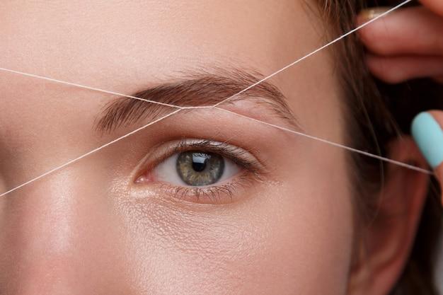 Augenbrauenkorrektur mit einem weißen faden