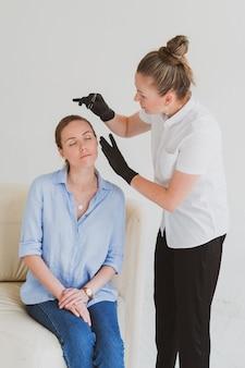 Augenbrauenmeister kosmetikerin modelliert die augenbrauen einer jungen frau
