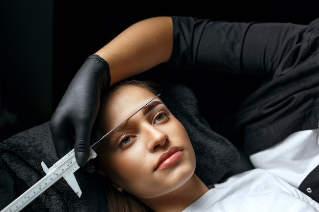 Augenbrauenstylist misst augenbrauen mit dem lineal vor dem permanent-make-up-verfahren in einem schönheitssalon