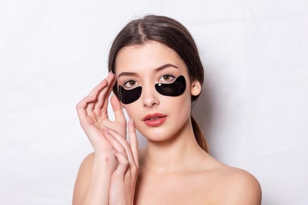 Augenklappe, schöne frau mit natürlichem make-up und schwarzen hydro-gel-augenklappen auf der gesichtshaut. kaukasische frau verwendet schwarze flecken nach dem duschen, hautpflege