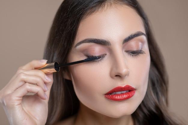 Augenkosmetik. gesicht der ernsthaften involvierten schönen frau mit hängenden augenlidern, die bürste mit wimperntusche nahe ihrem auge halten