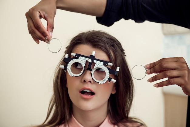 Augenpflege- und gesundheitskonzept. porträt der neugierigen und unterhaltenen jungen europäischen frau, die auf stuhl sitzt, während augenpflegespezialist sicht mit phoropter prüft und fragt, ob sie klar sehen kann