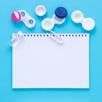Augenpflegezubehör auf blauem hintergrund mit notizbuchmodell