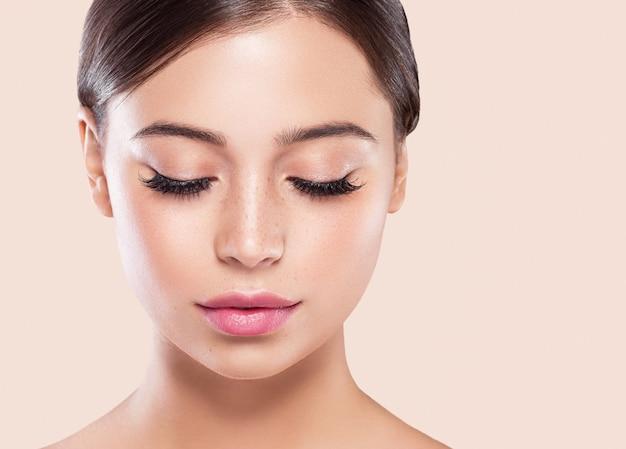 Augenwimpern frau gesicht nahaufnahme natürliche make-up gesunde haut. studioaufnahme. farbiger hintergrund.