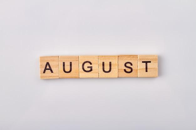 August wort geschrieben auf holzklötzen. auf weißem hintergrund isoliert.