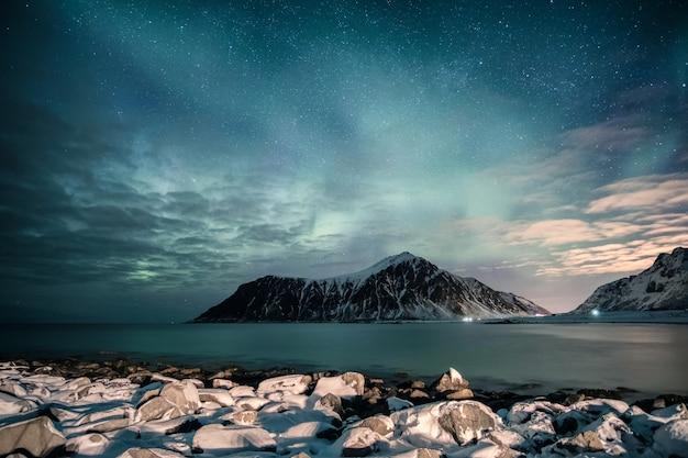 Aurora borealis mit sternen über gebirgszug mit schneebedeckter küstenlinie