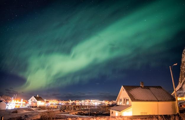 Aurora borealis tanzt über ein skandinavisches dorf