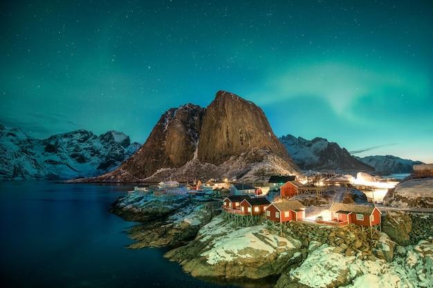 Aurora borealis über berg mit fischerdorf in hamnoy
