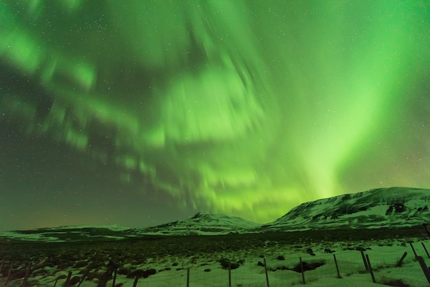 Aurora borealis über bergen im norden islands im winter