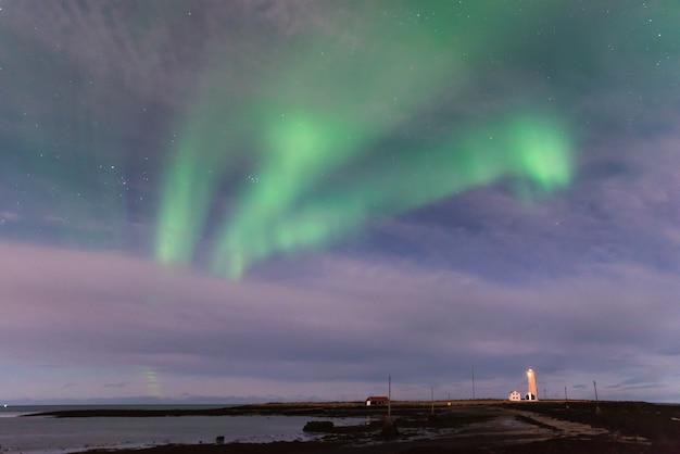 Aurora borealis über dem grotte-leuchtturm in island mit dem ozean und einem schwarzen sand beac