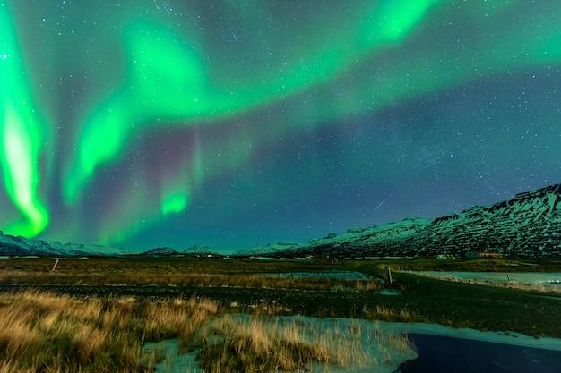 Aurora erhebt sich über einem schönen berg. in island