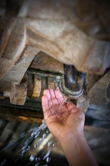 Aus dem alten straßenhahn fließt das wasser zur hand