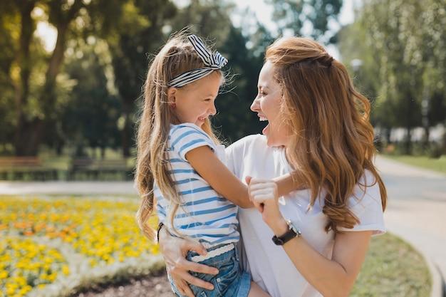 Aus dem kindergarten. ansprechende mutter, die fröhlich ist und ihr süßes kleines mädchen vom kindergarten nimmt