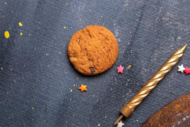 Aus der nähe ansicht köstlicher schokoladenplätzchen mit goldener kerze auf dem dunklen hintergrundplätzchenplätzchenzucker-teesüß
