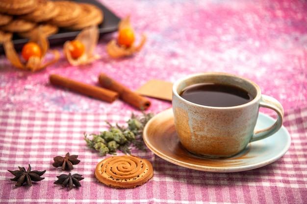 Aus der nähe ansicht süße kekse köstliche kleine kekse mit tasse tee auf hellrosa schreibtisch.