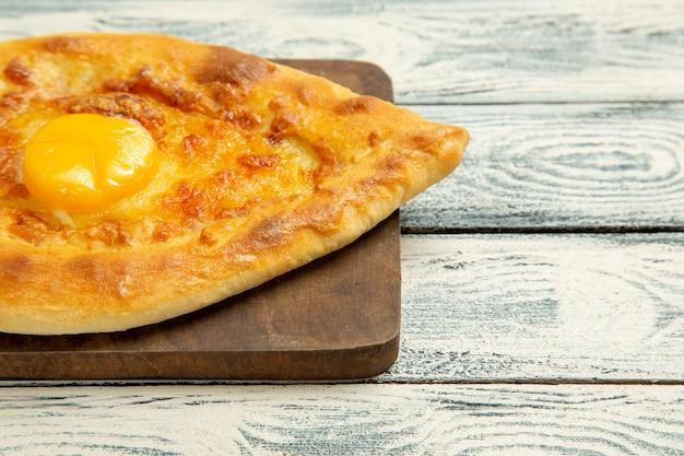 Aus der nähe gesehen köstliches eierbrot, das auf einem grauen rustikalen schreibtisch gebacken wird