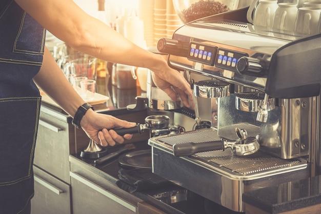 Aus der nähe macht barista einen espresso mit einer klassischen italienischen kaffeemaschine mit dampf und sonnenlicht