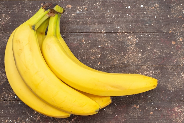 Aus der nähe sehen sie köstliche bananen auf braunem exotischem essen mit fruchtbeeren