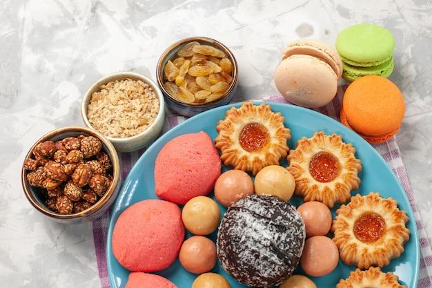 Aus der nähe sehen sie köstliche kuchen mit keksen und macarons auf dem weißen schreibtisch