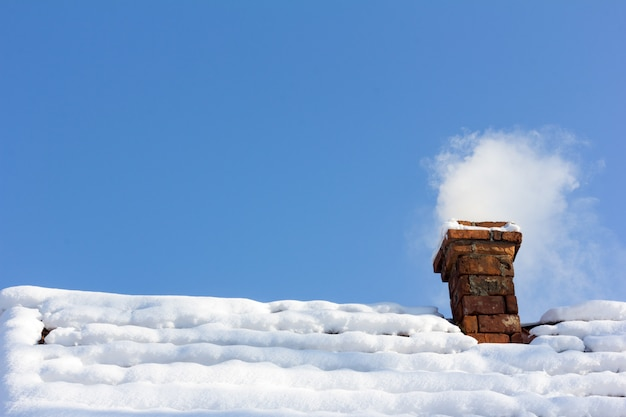 Aus einem gemauerten schornstein auf einem schneebedeckten dach rauchen