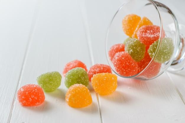 Aus einer glasschale auf einem weißen tisch gossen bunte marmeladenstücke. leckere süßigkeiten aus gelee mit zucker.