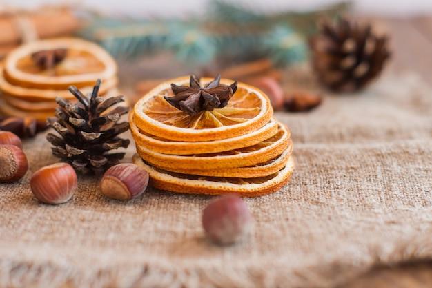 Aus getrockneten orangen, nüssen, anis-nelken und zapfen auf rustikalem sackleinen winter aromatische komposition