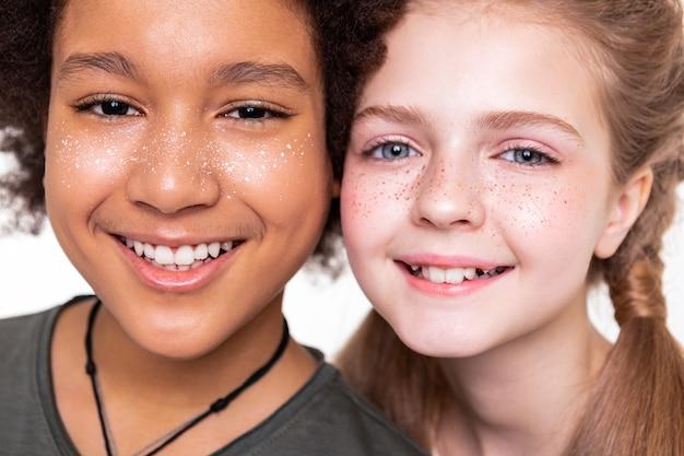 Aus nächster nähe posieren. angenehm gut aussehende kinder, die ihre starken weißen zähne zeigen, während sie in die kamera lächeln