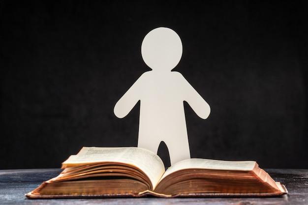 Aus papier geschnitzte figur eines mannes, der an einem aufgeschlagenen buch steht. das konzept des lernens und des wissens.