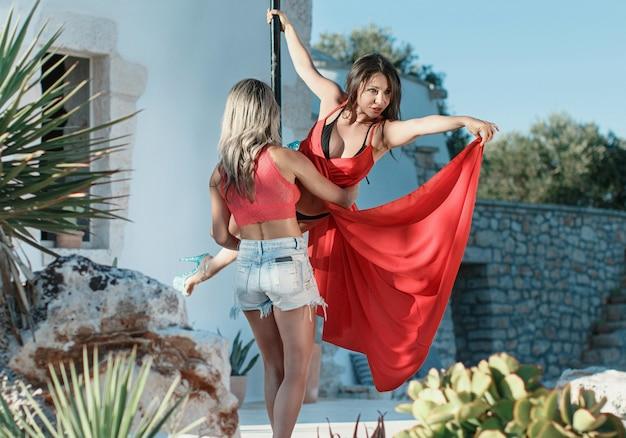 Ausbilder, der dem jungen stangentänzer in einem kleid hilft, auf einer tragbaren plattform gegen den garten eine pose einzunehmen