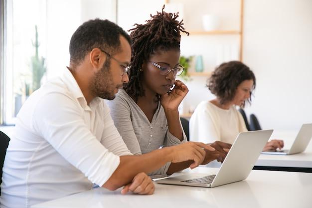 Ausbilder, der die firmenspezifische software für praktikanten erklärt